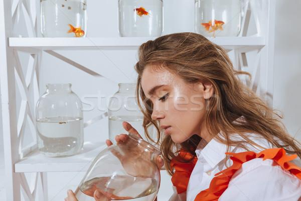 Aantrekkelijk jonge vrouw naar jar goud vis Stockfoto © deandrobot