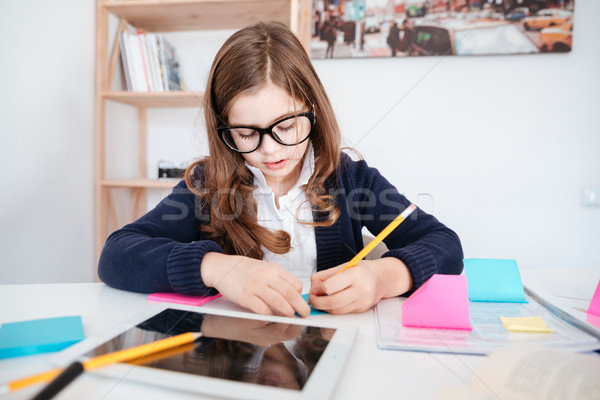 Girl with tablet sitting and writing at the table Stock photo © deandrobot
