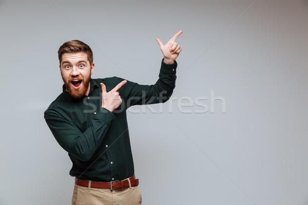 счастливым бородатый человека рубашку указывая далеко Сток-фото © deandrobot
