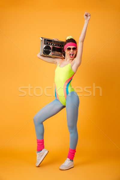 Full length of happy sportswoman holding old boombox and shouting Stock photo © deandrobot