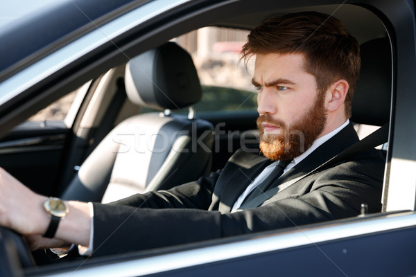 Portrait of a concentrated bearded man in suit driving car Stock photo © deandrobot