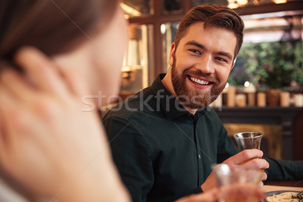 Smiling young loving couple sitting in cafe and eating Stock photo © deandrobot