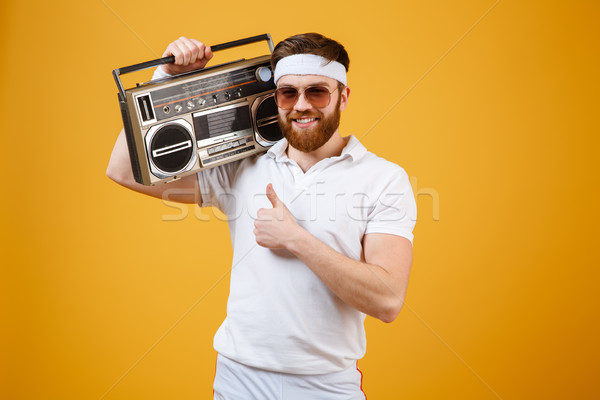 Man holding tape recorder make thumbs up gesture. Stock photo © deandrobot