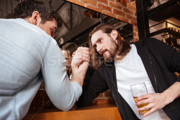 Drunk friends playing in arm wrestling Stock photo © deandrobot