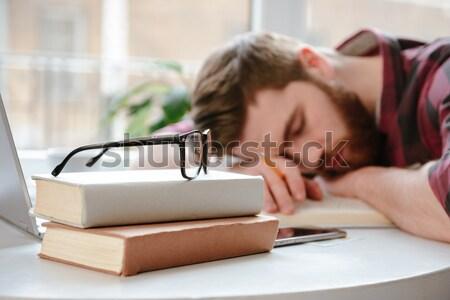 Cansado barbado joven estudiante mentiras manos Foto stock © deandrobot