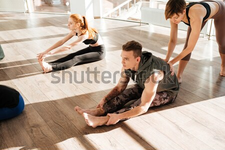 Barefoot african young man doing stretching yoga exercises with instructor Stock photo © deandrobot