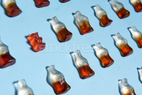 Sweeties chewing candy in bottle form over blue background. Stock photo © deandrobot