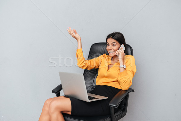 Happy businesswoman sitting with laptop and talking on mobile phone Stock photo © deandrobot