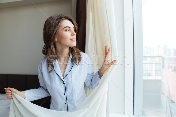Portrait of a happy woman opening window curtains Stock photo © deandrobot
