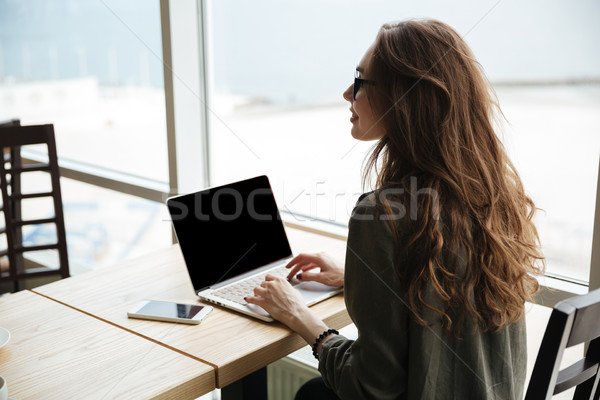 Back view of woman with blank screen of laptop Stock photo © deandrobot