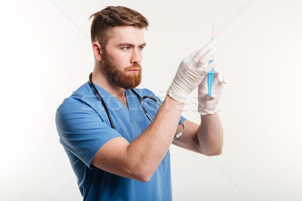 Portrait of a serious surgeon holding a syringe Stock photo © deandrobot