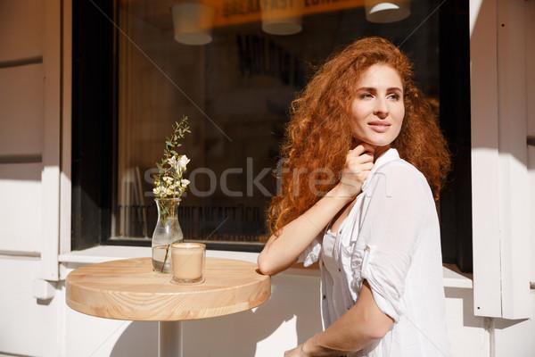Atraente mulher jovem cabelos cacheados sessão tabela retrato Foto stock © deandrobot