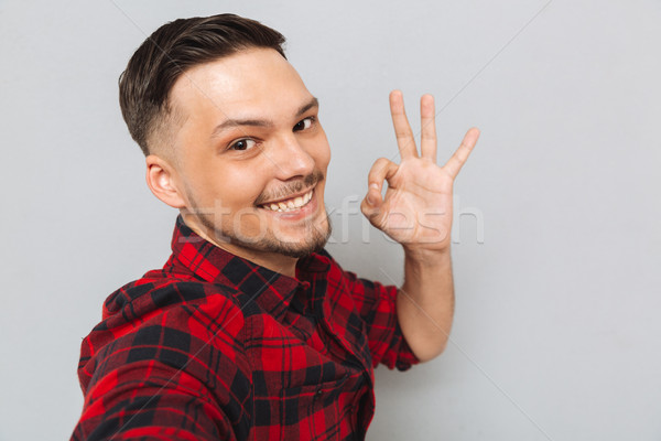 Smiling man standing sideways and showing ok sign Stock photo © deandrobot