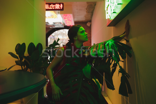 Side view of woman looking at Illuminated signboard Stock photo © deandrobot