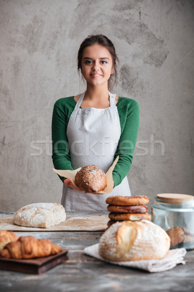 Stock photo: Cheerful lady baker standing and holding bread