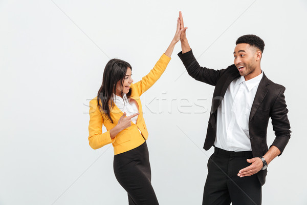 Happy colleagues business team gives a high-five to each other. Stock photo © deandrobot