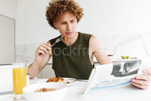 Férfi ül konyha eszik sütemények kép Stock fotó © deandrobot
