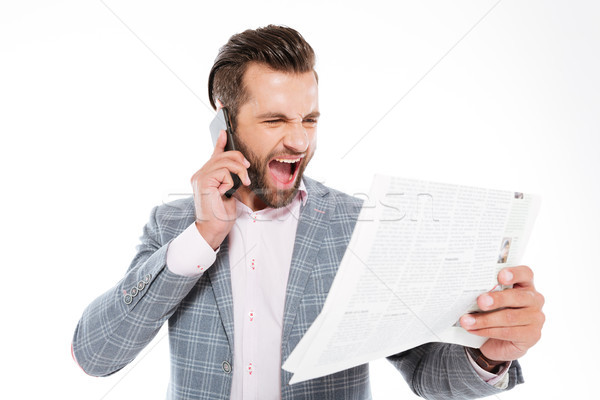 Screaming young man holding gazette and talking by phone Stock photo © deandrobot
