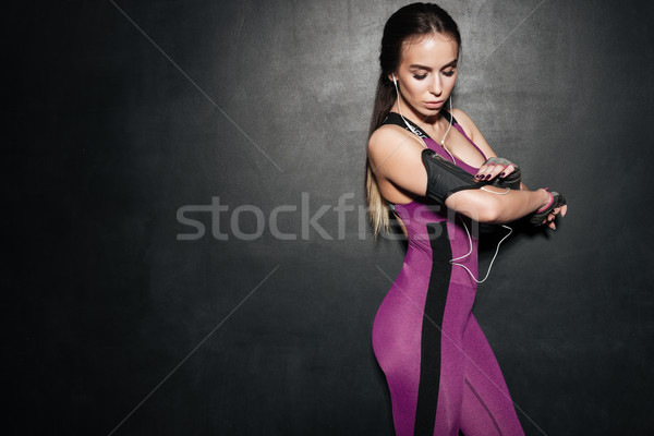 Young fitness woman with earphones adjusting her mobile phone Stock photo © deandrobot