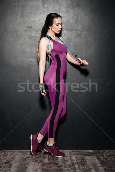 Concentrated sports young lady holding skipping rope. Stock photo © deandrobot