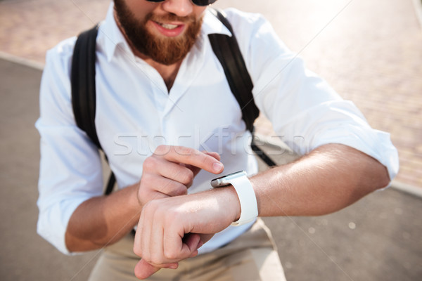 Cropped close up image of smiling bearded man using wristwatch Stock photo © deandrobot