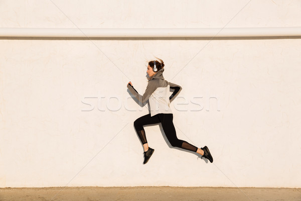Full length photo of young fitness woman in sport wear jumping n Stock photo © deandrobot