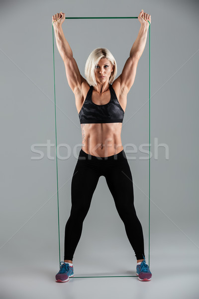 Full length photo of healthy fitness woman with raised arms stre Stock photo © deandrobot