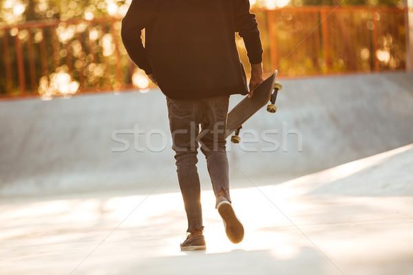 Kép fiatal afrikai férfi gördeszkás sétál Stock fotó © deandrobot