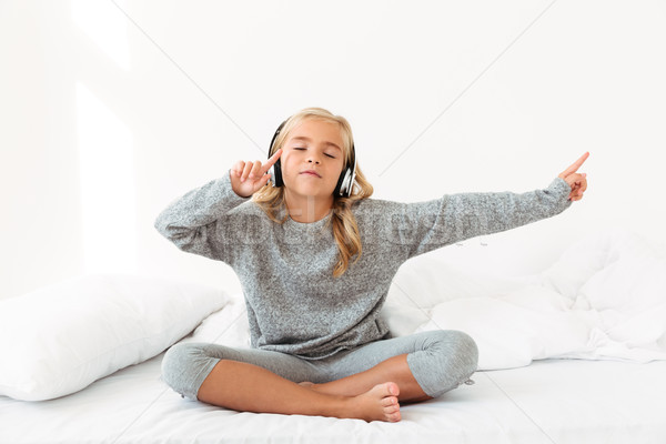 Cute little girl in gray pajamas listening to music with closed  Stock photo © deandrobot