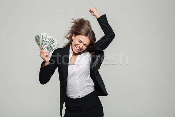 Portrait of a thrilled excited businesswoman in suit Stock photo © deandrobot