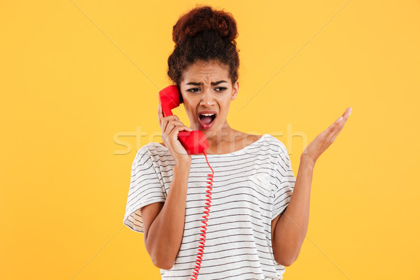 Angry african woman screaming while talking on red telephone Stock photo © deandrobot