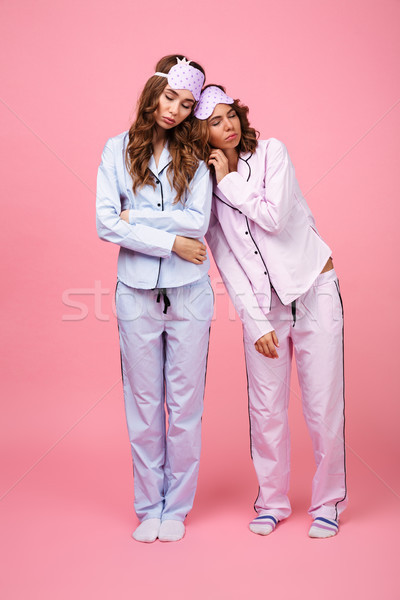 Two friends women in pajamas sleeping. Stock photo © deandrobot