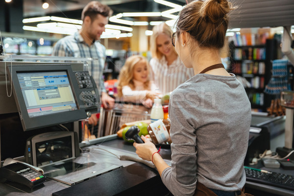 Beautiful family standing at the cash counter Stock photo © deandrobot
