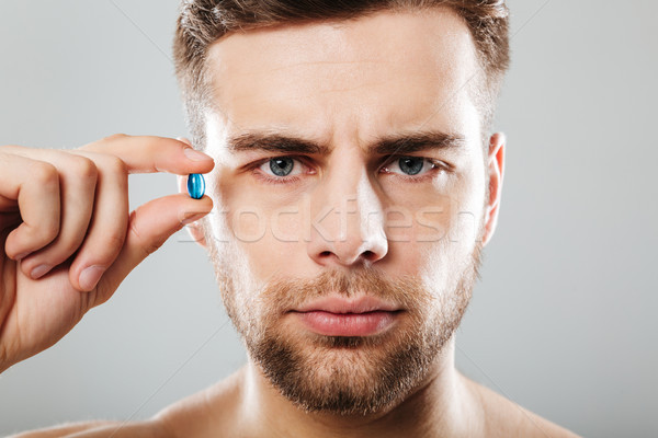 Portrait of a bearded man holding capsule at his face Stock photo © deandrobot