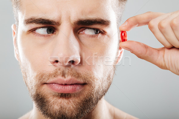 Close up portrait of a bearded man holding red capsule Stock photo © deandrobot