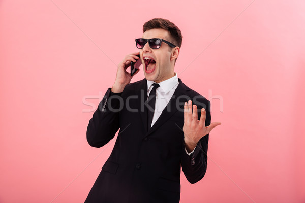 Happy man talking on smartphone and gesturing isolated Stock photo © deandrobot