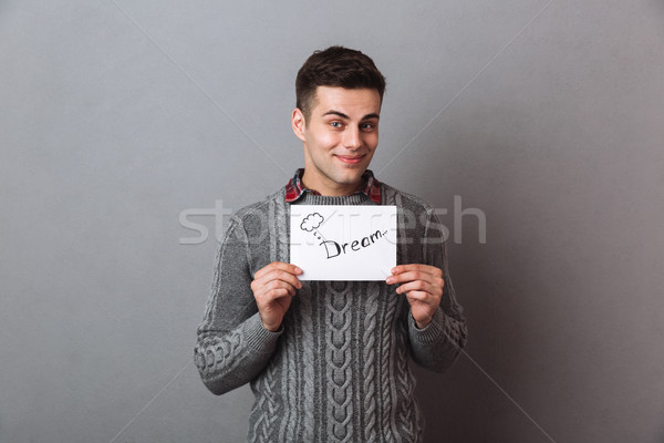 Handsome young cheerful man holding paper with dream text. Stock photo © deandrobot