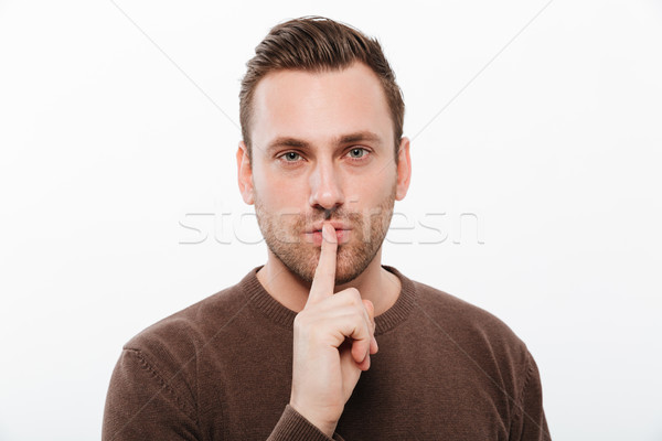 Handsome young serious man showing silence gesture Stock photo © deandrobot