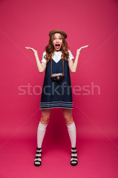Shocked lady with opened mouth looking camera while holding retro camera Stock photo © deandrobot