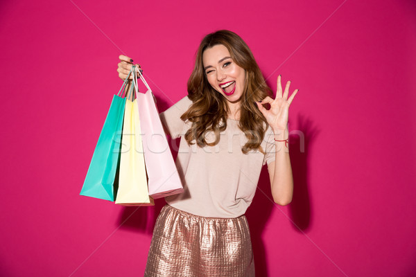 Smiling young woman holding shopping bags showing okay gesture. Stock photo © deandrobot