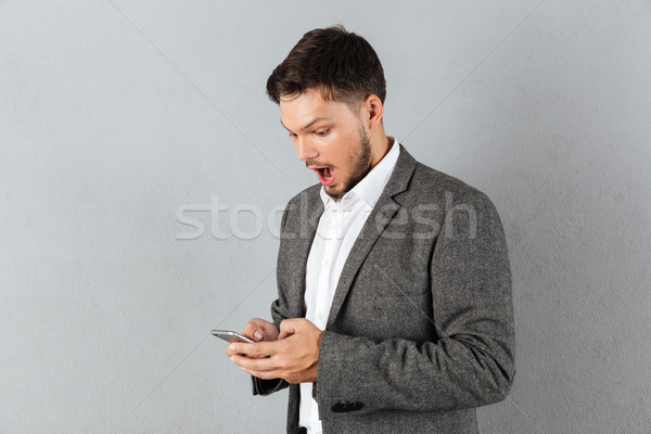 Stock photo: Portrait of a surprised businessman looking at mobile phone