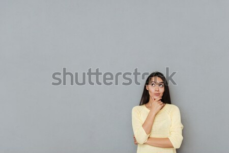Image of Pensive woman holding her chin and looking up Stock photo © deandrobot