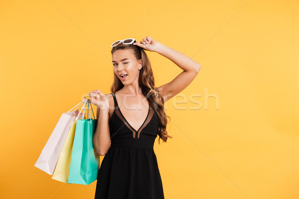 Amazing lady in black dress winking and holding shopping bags. Stock photo © deandrobot