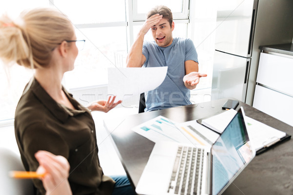 Young busy man has a quarrel with his woman while working at home Stock photo © deandrobot