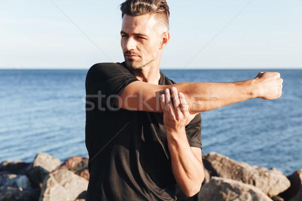 Koncentrált sportoló nyújtás tengerpart égbolt víz Stock fotó © deandrobot