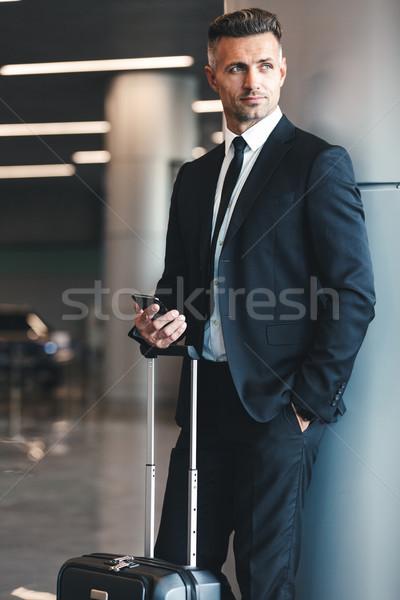 Successful mature businessman holding mobile phone Stock photo © deandrobot
