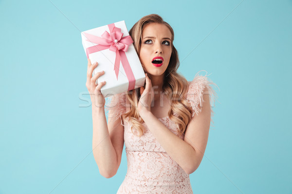 Intrigued blonde woman in dress holding gift and looking up Stock photo © deandrobot
