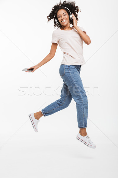 Full length photo of cheerful american woman with brown curly ha Stock photo © deandrobot