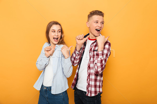 Stock photo: Portrait of a smiling teenage couple pointing fingers