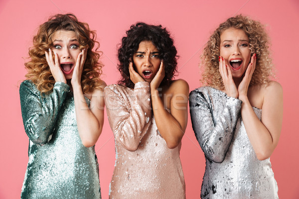 Three beautiful astonished women in shiny dresses Stock photo © deandrobot